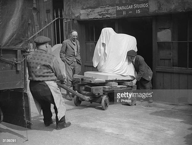 British sculptor Frank Dobson watches his works being removed from the Trafalgar Studios in London's Chelsea to be put on display at the Leicester...