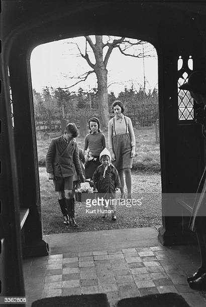 Children carrying in baskets of flowers to decorate the local church for a wedding between a soldier and his country bride at Solhamstead Berkshire...