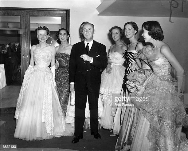 Fashion couturier Christian Dior designer of the 'New Look' and the 'Aline' with six of his models after a fashion parade at the Savoy Hotel London