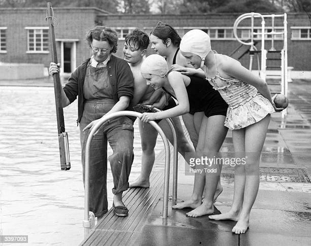 Lily Goodwin Deputy Superintendent of Brockwell Park openair swimming pool takes the temperature of the water on the first day of the summer season...