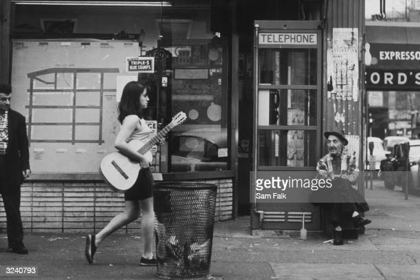 Street scene of a young woman walking with an acoustic guitar as an old man sits by a telephone booth in Greenwich Village New York City A man with a...