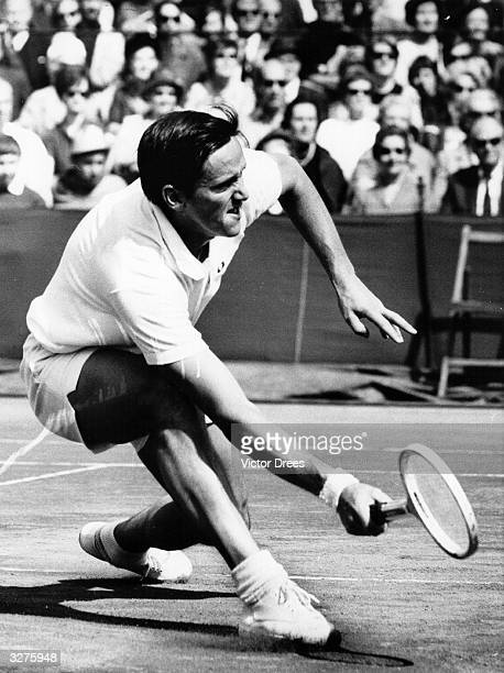 Australian tennis player Roy Emerson stoops for a low ball during a match at Wimbledon