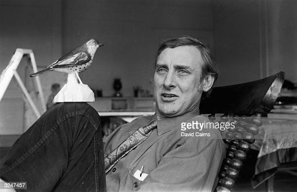Spike Milligan relaxes at home with a model bird on his knee