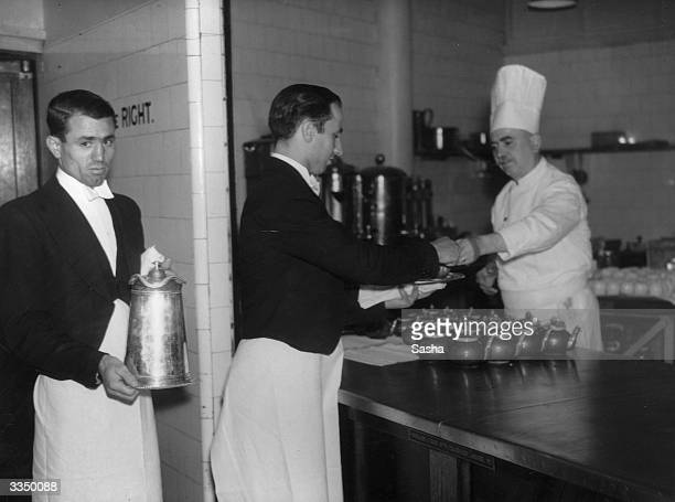 Waiters collecting hot beverages from a chef in the kitchen at the Savoy Hotel London