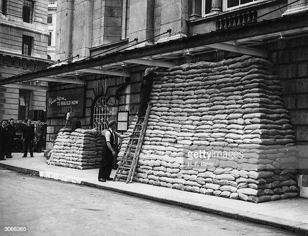 Workmen protect the walls of Mansion House in London with a barricade of sandbags