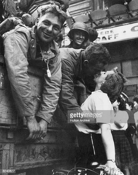 An American soldier leans over the side of an army vehicle as he kisses a French woman on a bicycle during the liberation of Paris. Other soldiers...