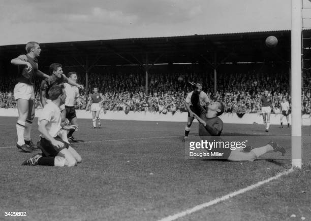Tottenham Hotspur footballer Terry Medwin on his knees as he scores against West Ham Bobby Moore looks on as goalkeeper Lawrie Leslie dives