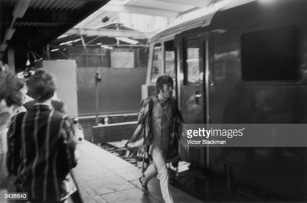 John Lennon of the Beatles hurries to catch a train to Bangor at Euston Station London
