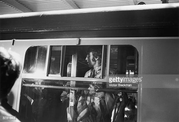 John Lennon of the Beatles standing by the window of a train at Euston Station shortly before departure to Bangor
