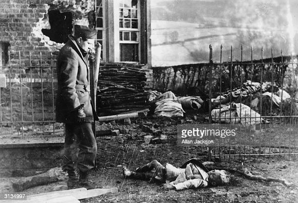 An American soldier looks down at the body of a little boy in a yard in Stavelot Belgium The child along with the other civilians in the background...
