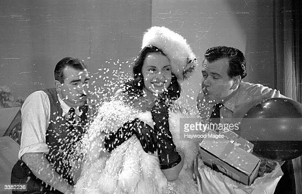 Actress Patricia Plunkett sits in a flurry of fake snow during a Christmas photo shoot The photograph will be used by film company ABC as a Christmas...