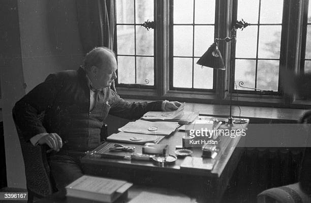 British statesman Winston Churchill sits at the writing desk of his country home in Chartwell, Kent. On the desk can be seen medals awarded to him...