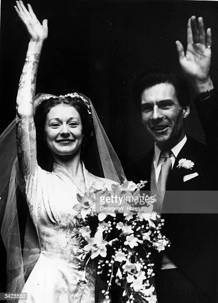 British ballerina Moira Shearer and her husband broadcaster Ludovic Kennedy wave to ballet fans after their wedding at the Chapel Royal Hampton Court...