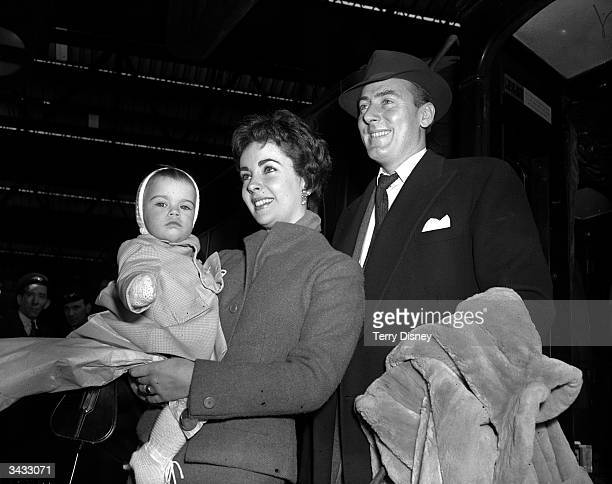 Film star couple Elizabeth Taylor and Michael Wilding pose with their son Michael Wilding Jnr at London's Waterloo Station en route to the States
