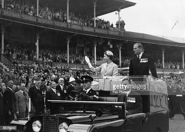 Queen Elizabeth II and Prince Philip wave to crowds as they are driven on a circuit of Melbourne cricket ground as part of their Australian tour The...