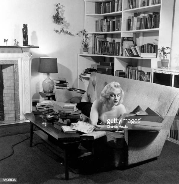 English actress Sabrina originally Norma Sykes lying reading on a sofa Original Publication Picture Post 8276 Sabrina A Cult Takes To Culture pub 1956