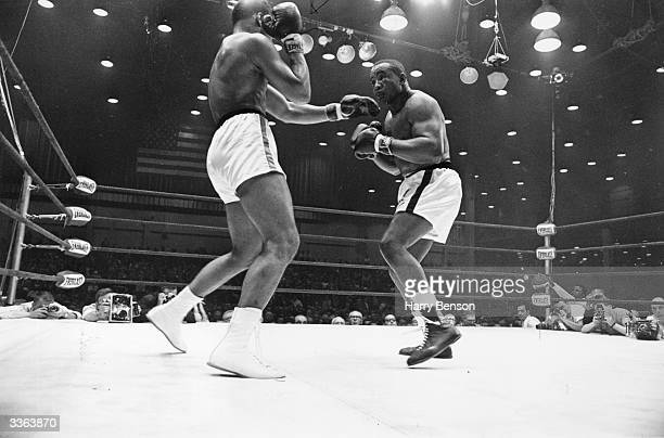 American boxer Cassius Clay later Muhammad Ali in action against Sonny Liston during their heavyweight title fight at Miami Beach Florida Clay won...