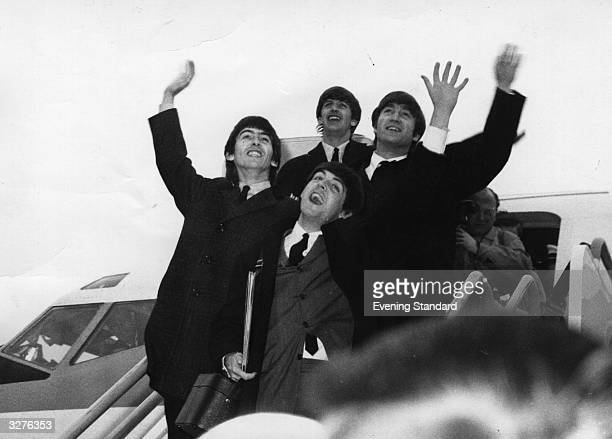 The Beatles on the steps of an aeroplane waving to their fans