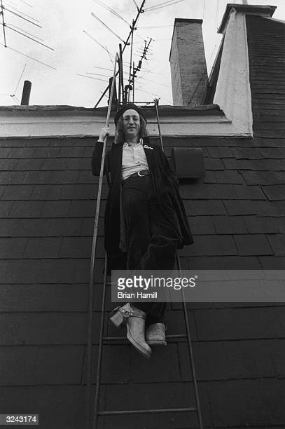 British rock singer and songwriter John Lennon smiles as he stands on a ladder on the roof of his apartment building the Dakota New York City He...