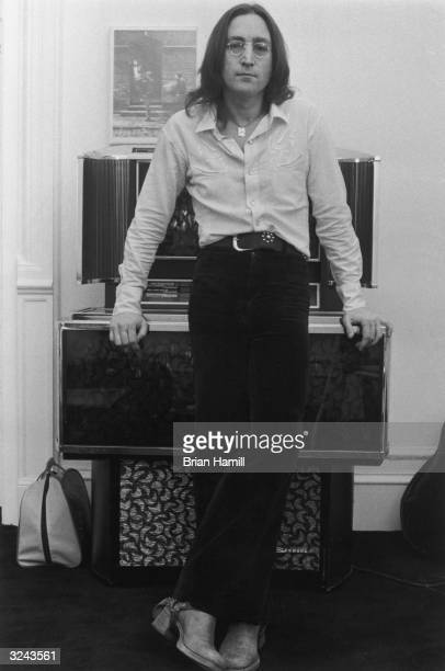 Fulllength portrait of British rock singer and songwriter John Lennon leaning on a jukebox at his apartment in the Dakota New York City He wears a...