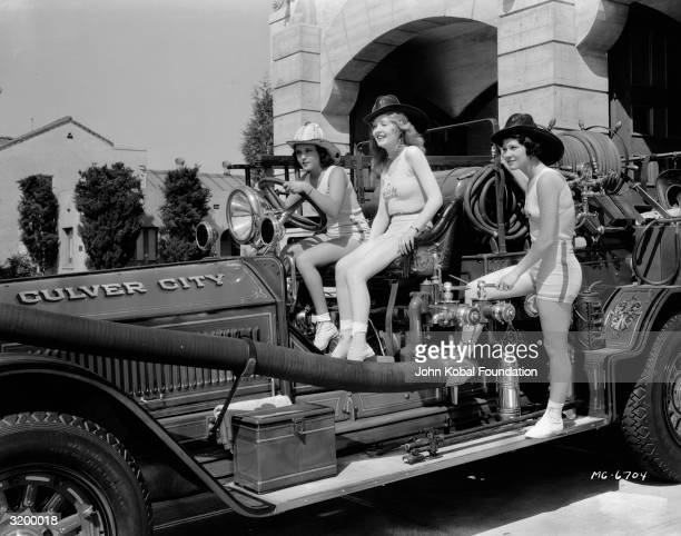 Three women in shorts and vest tops man a Culver City fire engine in California Culver City is home to the MGM studios