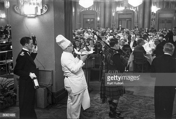 The haggis is served to the guests during Burns Night at the Pavilion Restaurant Bournemouth A bagpipe player serenades the entrance of the chef...
