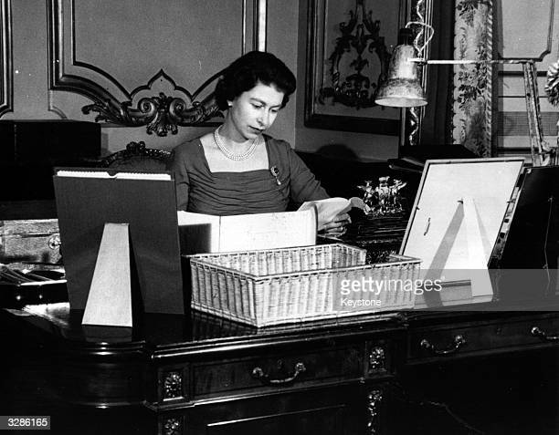 Queen Elizabeth II reading the contents of her official boxes containg details of her country's political affairs at her desk in Buckingham Palace...