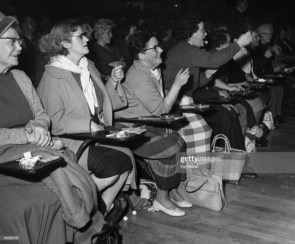An excited group of women betting on American horse races, which they are watching at a British cinema.