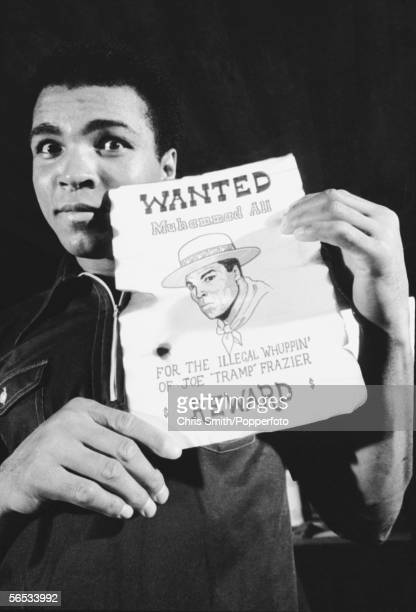 American heavyweight boxing champion Muhammad Ali holds up a tongueincheek Wanted poster with a reward for his own capture shortly before his rematch...
