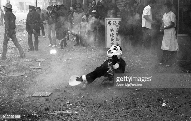 A masked street performer dances on the sidewalk as firecrackers explode all around him during the annual Chinese New Year celebrations in Chinatown...