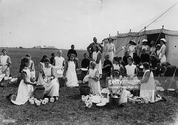 Group of girls and boys from the Islington workhouse at camp on Canvey island on the River Thames London Boys and girls in their pinafores are doing...