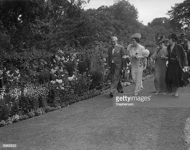 Queen Elizabeth , Queen Consort to King George VI walking with her hosts at a garden party.