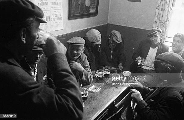 A group of pea pickers enjoying a beer in one of the few pubs which will serve them They belong to a band of nomads whose homes are in the hedgerows...
