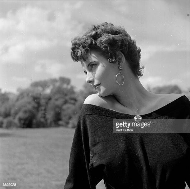 A woman modelling the latest hairstyle the Spanish cheekbone curl with a pair of gypsy earrings Original Publication Picture Post 6600 Headlining The...