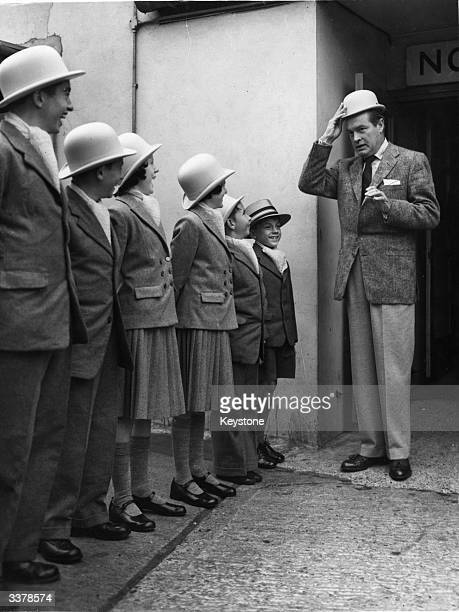 American actor and comedian Bob Hope is greeted on his arrival at London Airport by seven children in honour of his latest film 'Seven Little Foys'...