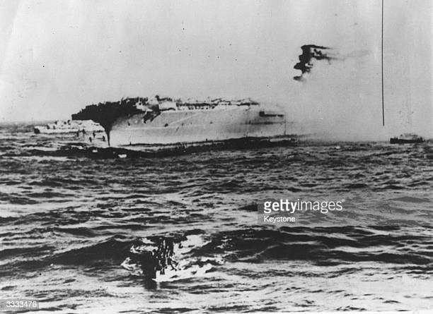 USS 'Lexington' burning in the background and survivors being rescued by launches one seaman is being towed during the fighting in the Coral Sea