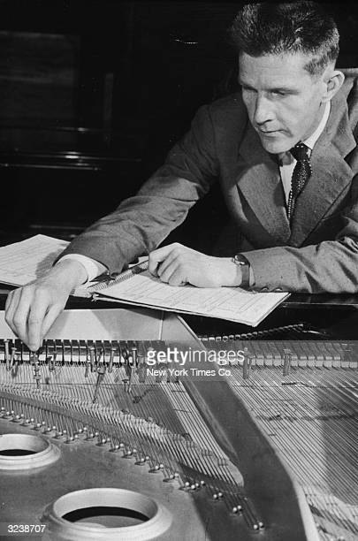 American author and experimental composer John Cage Jr changing the tuning of his piano by placing coins and screws between the strings in Gaveau...