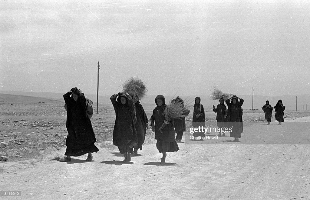 Palestinian refugees trek across the scorching heat of Jordan near the shores of the Dead Sea in the year following the Arab Israeli War at the time of the creation of the State of Israel. Original Publication: Picture Post - 4818 - Who'll Help The Refugee Arabs? - pub. 1949