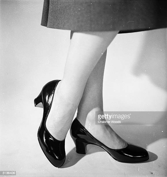 A woman's legs wearing a pair of patent leather shoes