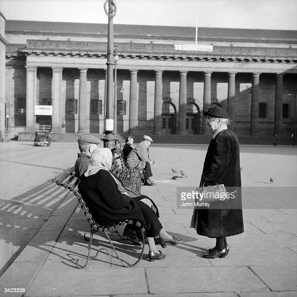 A group of elderly folk sitting on a bench in a Dundee square Dundee situated on the banks of the dSilvery Tayf is linked to Fife and the south of...
