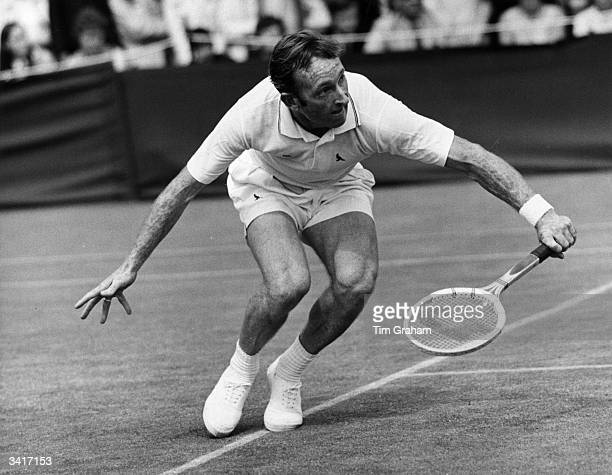 Australian tennis star Rod Laver stoops low to reach a return during a match against P Lall at Wimbledon