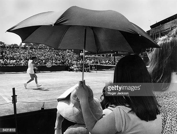 A spectator at the Wimbledon Lawn Tennis Championships using an umbrella to shelter from the sun as Marise Kruger of South Africa plays a match