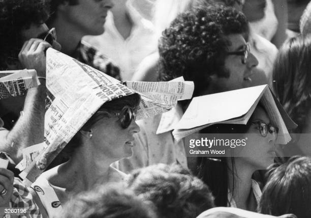 Spectators at Wimbledon Tennis Championships protect themselves from the sun wearing newspaper hats and books on their heads during the heatwave