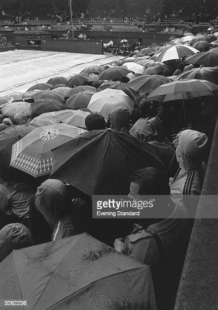 Spectators take shelter from the rain under umbrellas at Wimbledon, as they wait for play to resume on the Centre Court.