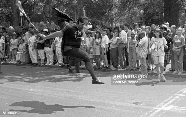 A man dressed as Batman enthusiastically jumps into the air in celebration at the 1989 Gay Pride Parade in Greenwich Village Manhattan commemorating...