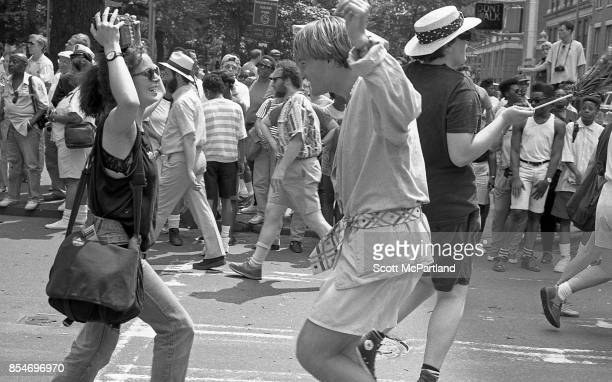 A woman holding a radio over her head and a man dance in the middle of the street during the 1989 Gay Pride Parade in Greenwich Village Manhattan...