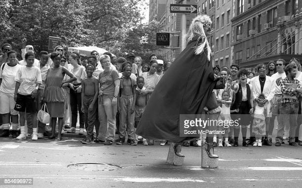 Dozens of smiling and laughing onlookers line Washington Square Park as a man dressed in drag walks by during the 1989 Gay Pride Parade in Greenwich...