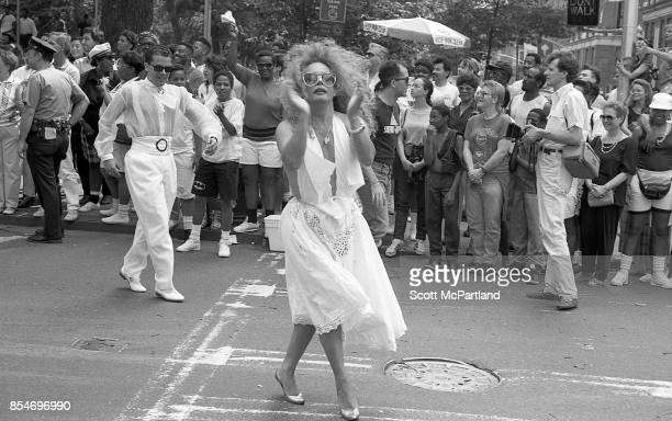 Gay rights activists dance in the street in front of dozens of onlookers in Greenwich Village Manhattan at the 1989 Gay Pride Parade commemorating...