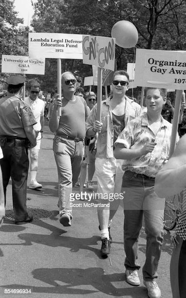 Groups of activists march down the streets of Greenwich Village NYC with signs held high during the 1989 Gay Pride Parade commemorating the 20th...
