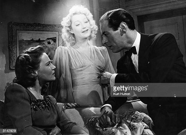 Kay Hammond appears as a ghost eavesdropping on Rex Harrison's conversation with his new wife Ruth Condomine in a scene from David Lean's 'Blithe...